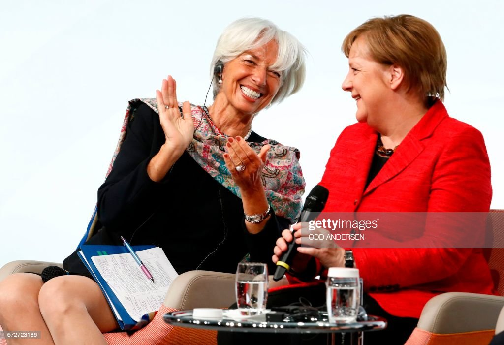 The Managing Director of the International Monetary Fund (IMF) Christine Lagarde and German Chancellor Angela Merkel share a laugh at the start of a panel discussion at the W20 women's empowerment summit sponsored by the Group of 20 major economic powers on April 25, 2017 in Berlin. On her first official trip as presidential adviser, Ivanka Trump appeared on a panel with high-powered guests, also including IMF chief Christine Lagarde and Queen Maxima of the Netherlands, on Women's Economic Empowerment and Entrepreneurship. / AFP PHOTO / Odd ANDERSEN