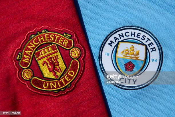 The Manchester City and Manchester United club crests on first team home shirts on April 24, 2020 in Manchester, England