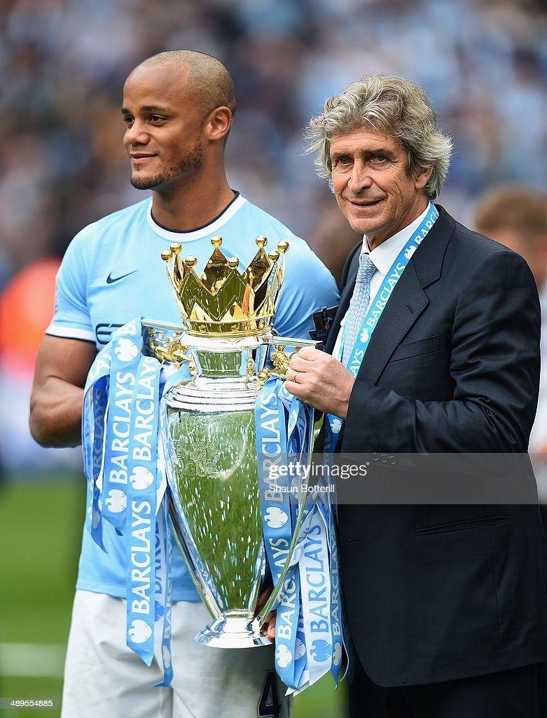 The Manchester City Manager Manuel Pellegrini and Vincent Kompany pose with the trophy at the end of the Barclays Premier League match between Manchester City and West Ham United at the Etihad Stadium on May 11, 2014 in Manchester, England.