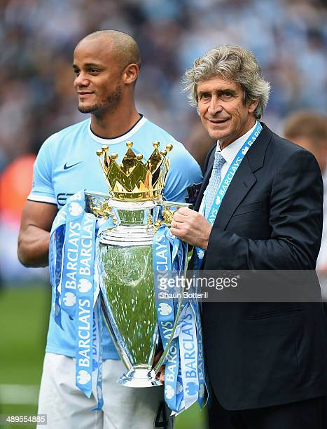 The Manchester City Manager Manuel Pellegrini and Vincent Kompany pose with the trophy at the end of the Barclays Premier League match between...