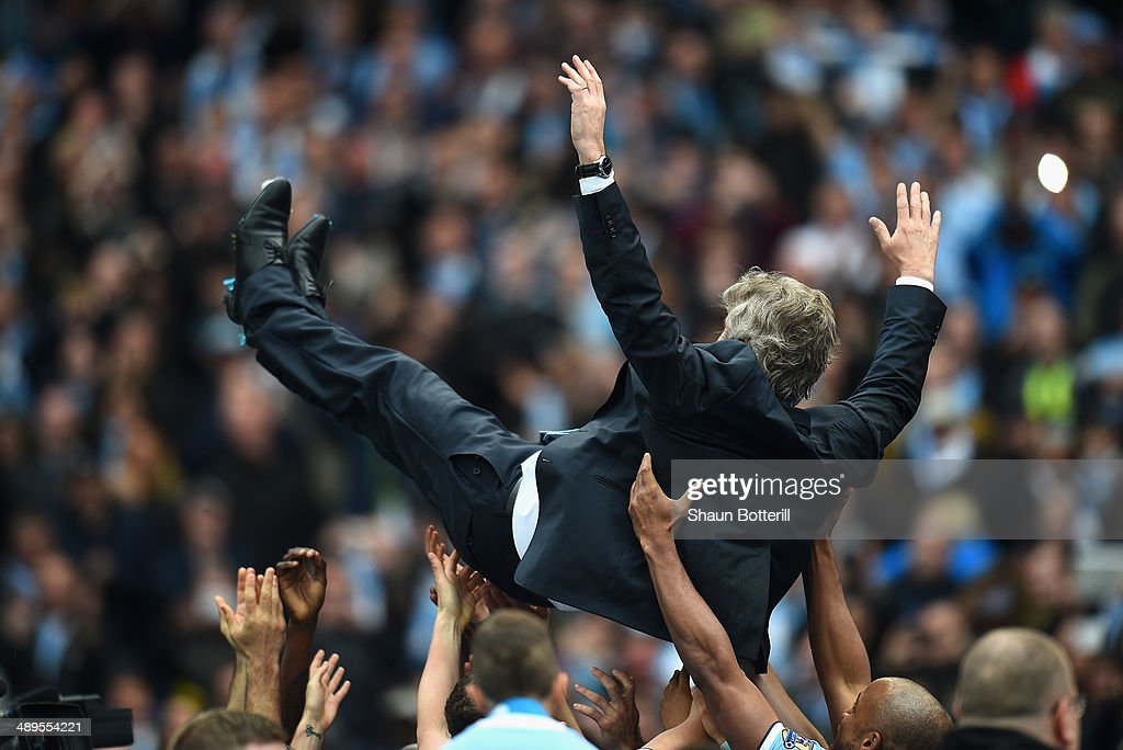 The Manchester City Manager Manuel Pellegrini is thrown in the air by his players at the end of the Barclays Premier League match between Manchester City and West Ham United at the Etihad Stadium on May 11, 2014 in Manchester, England.