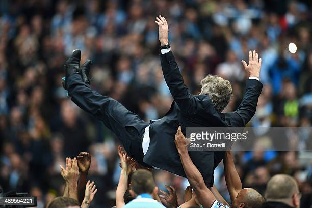 The Manchester City Manager Manuel Pellegrini is thrown in the air by his players at the end of the Barclays Premier League match between Manchester...
