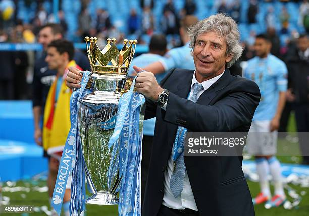 The Manchester City Manager Manuel Pellegrini poses with the Premier League trophy at the end of the Barclays Premier League match between Manchester...
