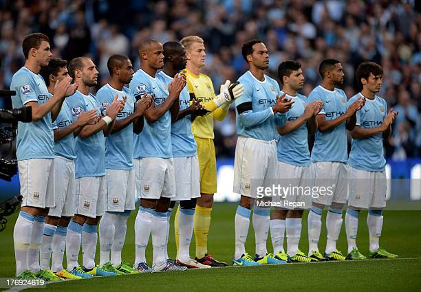 The Manchester City players applaud the memory of Bert Trautmann the former goalkeeper who died in July prior to the Barclays Premier League match...