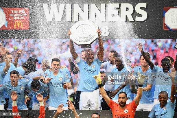 The Manchester City players celebrate as Vincent Kompany of Manchester City lifts the trophy following victory during the FA Community Shield between...