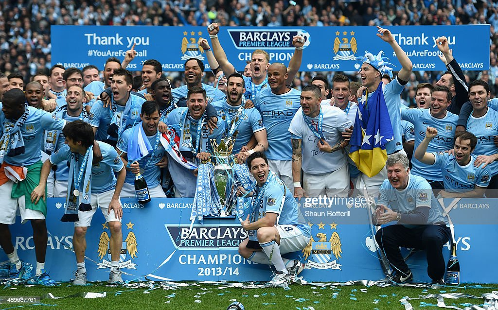 The Manchester City players celebrate with the Premier League trophy at the end of the Barclays Premier League match between Manchester City and West Ham United at the Etihad Stadium on May 11, 2014 in Manchester, England.