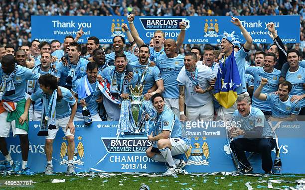 The Manchester City players celebrate with the Premier League trophy at the end of the Barclays Premier League match between Manchester City and West...