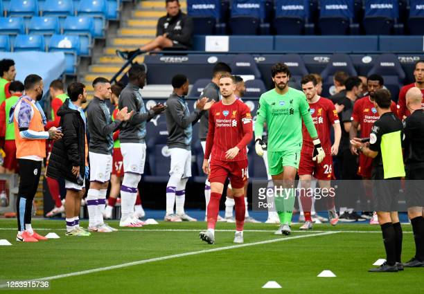 The Manchester City team create a guard of honor for the Liverpool FC team as Jordan Henderson of Liverpool leads his team out prior to the Premier...