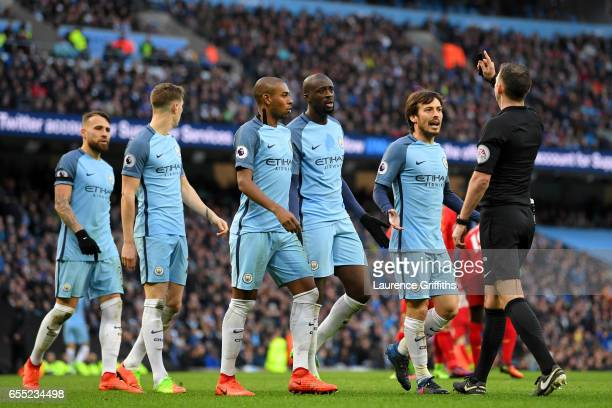 The Manchester City team plead with referee Michael Oliver after he awards a penalty to Liverpool during the Premier League match between Manchester...