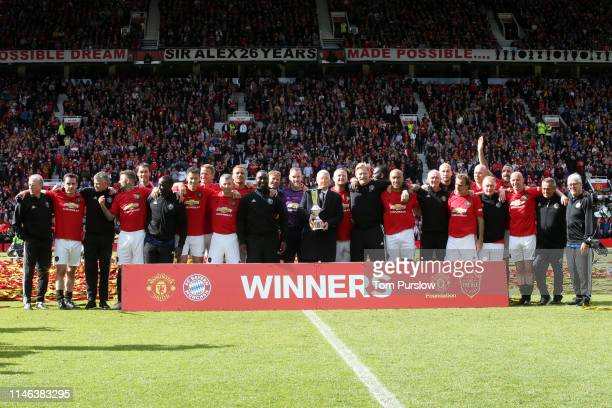The Manchester United '99 Legends pose with the trophy and Manager Sir Alex Ferguson at the end of the 20 Years Treble Reunion match between...