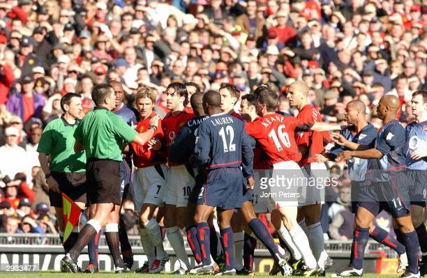 The Manchester United and Arsenal players confront referee Jeff Winter over a decision during the FA Cup 5th Round between Manchester United v...