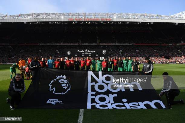 The Manchester United and Watford players stand with the match officials in protest against racism prior to the Premier League match between...