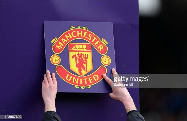 The Manchester United club badge is put up on the board during the Premier League match between Fulham FC and Manchester United at Craven Cottage on...