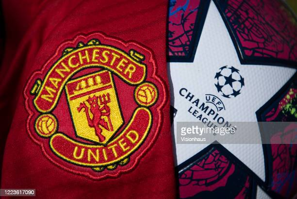The Manchester United club crest on the first team home shirt displayed with a UEFA Champions League match ball on May 5 2020 in Manchester England