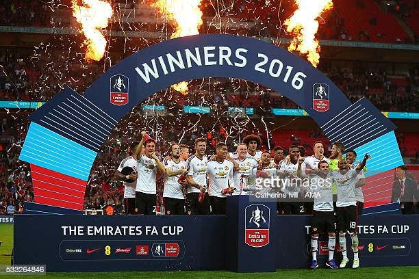The Manchester United players celebrate with the trophy following their 12 victory at the end of extra time during The Emirates FA Cup final match...