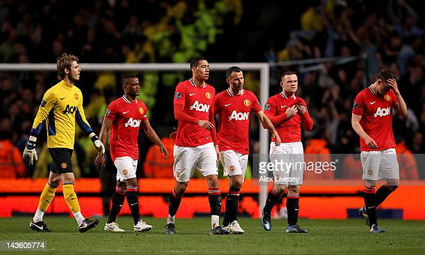 The Manchester United players look dejected at the end of the Barclays Premier League match between Manchester City and Manchester United at the...