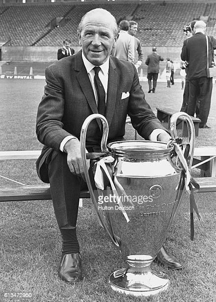 The Manchester United soccer team manager Sir Matt Busby proudly sits with the European Cup trophy won by his team in 1968