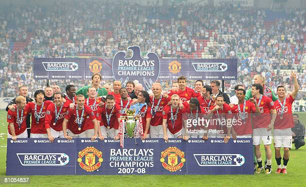 The Manchester United squad celebrate on the pitch with the Premiership trophy after the Barclays FA Premier League match between Wigan Athletic and...