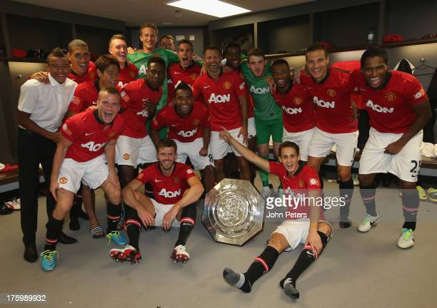 The Manchester United squad celebrate with the FA Community Shield trophy in the dressing room after the FA Community Shield match between Manchester...