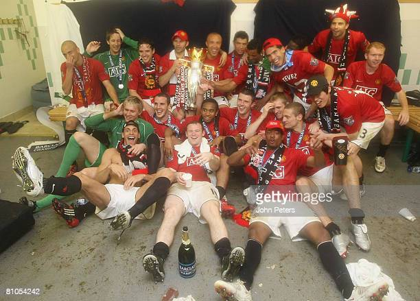 The Manchester United squad celebrate with the Premier League trophy in the dressing room afetr the Barclays FA Premier League match between Wigan...