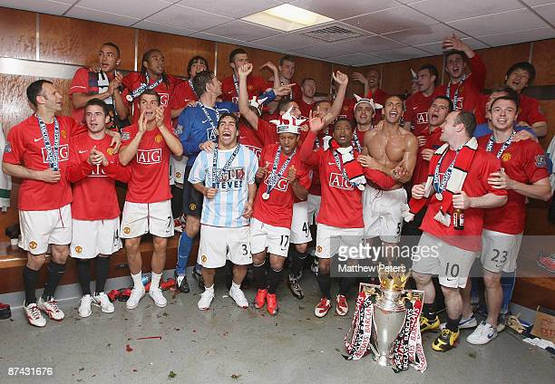 The Manchester United squad celebrate with the Premier League Trophy in the dressing room after the Barclays Premier League match between Manchester...