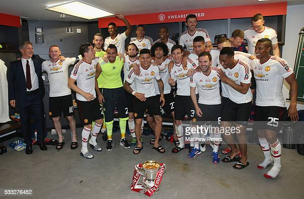 The Manchester United squad celebrates in the dressing room with the FA Cup trophy after The Emirates FA Cup final match between Manchester United...