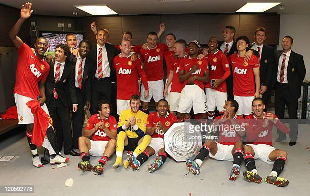 The Manchester United squad pose in the dressing room with the Community Shield trophy after the FA Community Shield match between Manchester City...