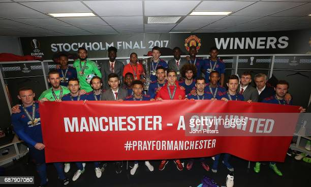 The Manchester United squad pose with a banner reading Manchester A City United PrayforManchester and the Europa League trophy after the UEFA Europa...