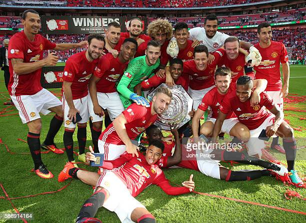 The Manchester United squad pose with the Community Shield trophy after the FA Community Shield match between Leicester City and Manchester United at...
