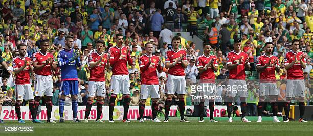 The Manchester United take part in a minute's applause in memory of former player Errol Crossan of Norwich City during the Barclays Premier League...