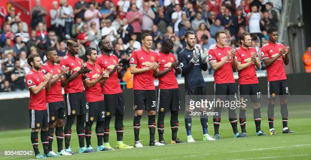 The Manchester United team take part in a minute's applause ahead of the Premier League match between Swansea City and Manchester United at Liberty...