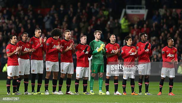 The Manchester United team take part in a minute's applause for former player Bill Foulkes ahead of the Barclays Premier League match between...