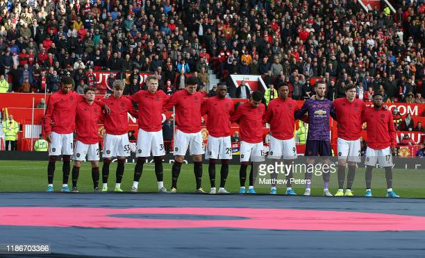 The Manchester United team take part in a minute's silence to mark Remembrance Sunday ahead of the Premier League match between Manchester United and...