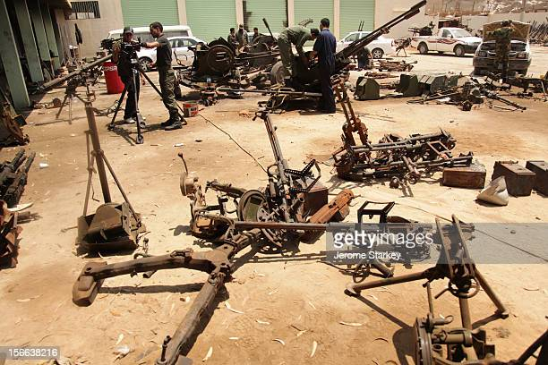 The mangled and rusty remains of Colonel Gaddafi's old weapons litter a workshop courtyard in Benghazi Libya where civil engineers are working...