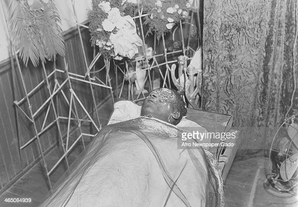 The mangled body of an African American lynching victim with a battered face displayed in a funeral home Monroe Georgia August 10 1946