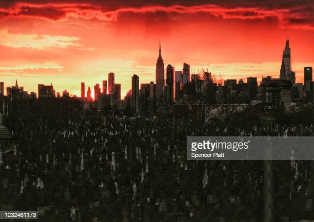 The Manhattan skyline is seen behind the tombstones at Calvary Cemetery on April 21, 2021 in the Queens borough of New York City.