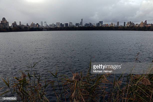 The Manhattan skyline is seen from the Jacqueline Kennedy Onassis Reservoir at Central Park as a construction crane hangs off of the side of One57 on...