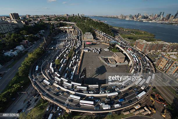 The Manhattan skyline stands past buses and cars sitting in traffic at the Lincoln Tunnel in this aerial photograph taken above Weehawken US on...