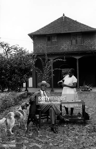 The manufacturer of agricultural rum La Mauny sitting beside his two dogs while his wife pouring rhum in a glass Martinique 1950s