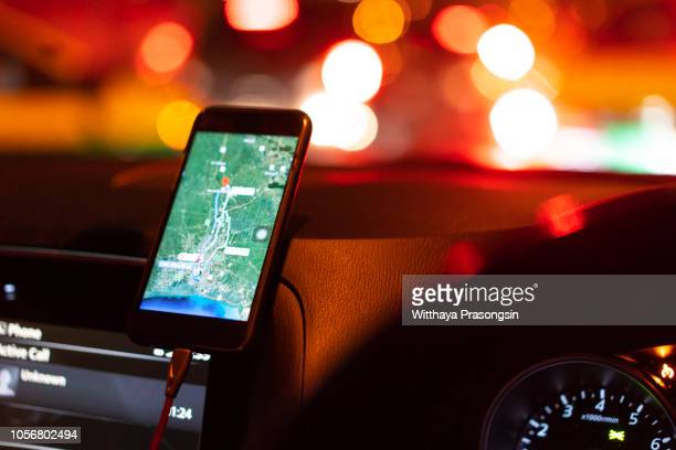 the map on the phone in the background of the dashboard. black mobile phone with map gps navigation fixed in the mounting. app map for travel. - karte navigationsinstrument stock-fotos und bilder