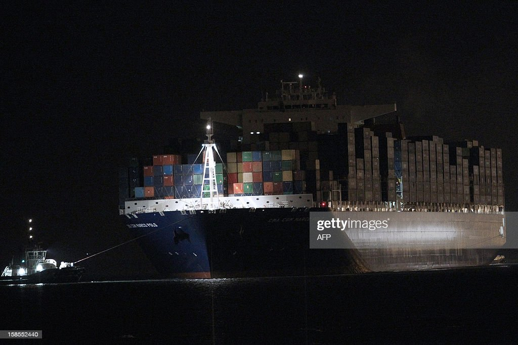 The Marco Polo, flying a British flag and said to be the world's biggest container ship by French owners CMA CGM, is towed into the port of Le Havre, western France, early on December 19, 2012