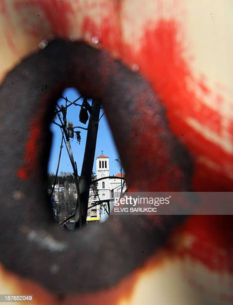 The Marijin Dvor square in Sarajevo is seen through a 20 year old shrapnel hole in a building currently under renovation on April 2, 2012. Sarajevo's...