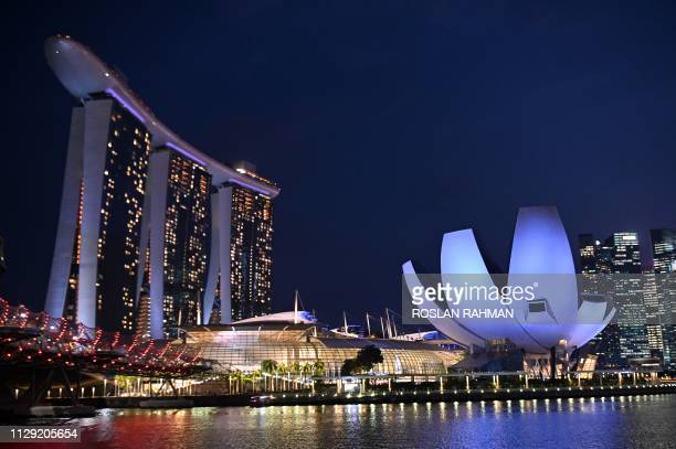The Marina Bay Sands hotel and resorts and the ArtScience Museum are illuminated under the evening sky in Singapore on March 8, 2019.
