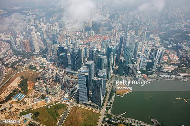 The Marina One development front left stands under construction next to commercial buildings in the central business district near Marina Bay in this...
