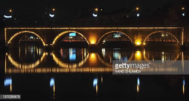 The Marjanishvili bridge is reflected in the Kura river in Tbilisi early on January 15 2012 AFP PHOTO / VANO SHLAMOV
