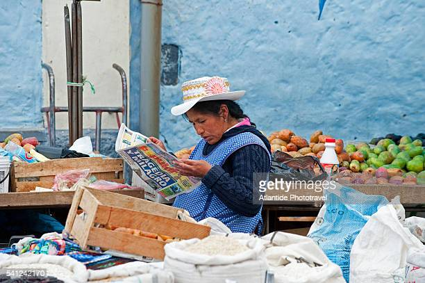 The market, a woman reading a newspaper