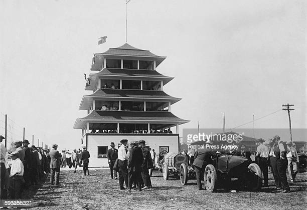The Marmon Wasp winner of the first Indianapolis 500 mile race sits in the paddock with the 1912 race winning National beneath the race control...