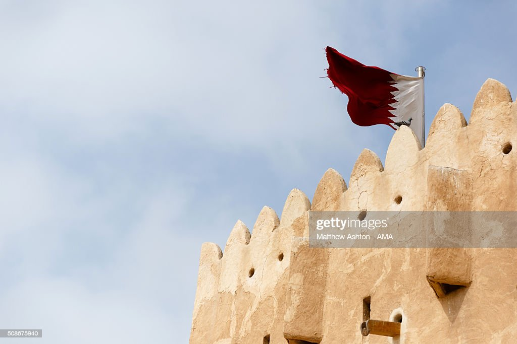 The maroon and white national flag of Qatar flying at the Al Zubarah Fort, a UNESCO World Heritage Site, in Madinat ash Shamal, Qatar. The country of Qatar is the host nation for the FIFA 2022 World Cup on January 25, 2016 in Qatar.