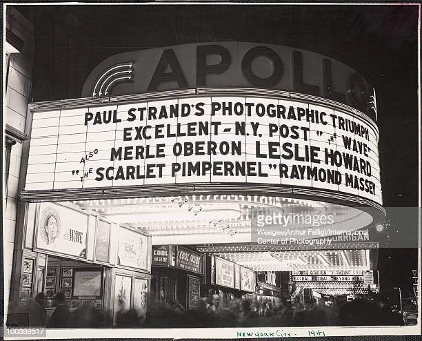 The marquee for the Apollo Theater lit up at night with a crowd milling about outside the theater located in Times Square New York 1941 The marquee...