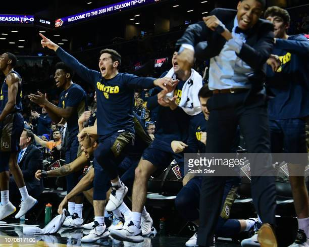 The Marquette Golden Eagles bench reacts during the first half of the game against Kansas Jayhawks during the NIT Season TipOff tournament at...